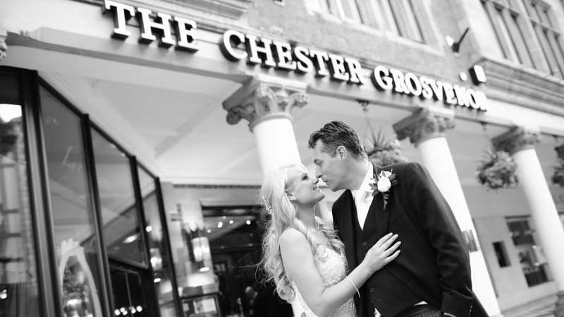 The Just Married Bride And Groom kiss outside The Chester Grosvenor