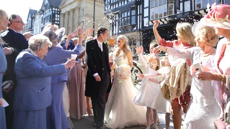 Family and Friends throw confetti on the bride and groom